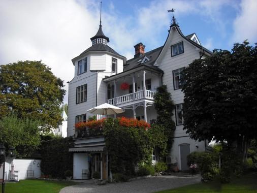 Stort vitt hus med trädgård