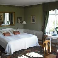 Sovrum med stor säng med vitt överkast och gula kuddar