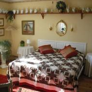 Sovrum med stor säng med rutigt överkast