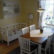 Matbord med vita stolar och en kökssoffa