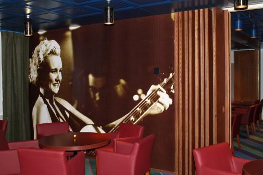 Lounge med röda fåtöljer och en svartvit bild på Eva Dahlgren