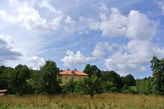 Gul byggnad omgiven av träd och blå himmel