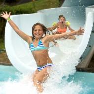 Glada barn som åker vattenrutschkana