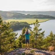 Man med ett barn på axlarna som tittar ut över ett landskap med vatten och skog