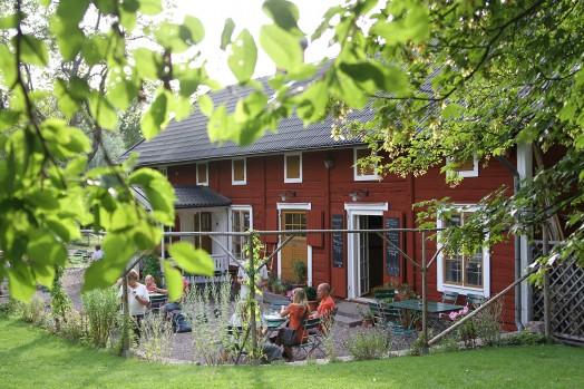 Gammal röd byggnad omgiven av grönska