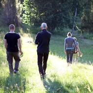 Fyra personer vandrar mot skogen i motljus