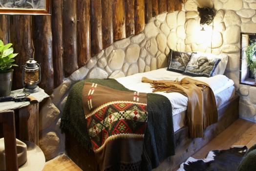Säng med vägg bakom gjord av sten och träd