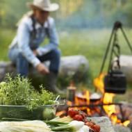 Cowboy vid eld i bakgrunden och ett bord med mat i förgrunden