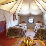 Luftigr rum med två sängar och en eld på golvet