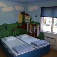 Rum med två enkelsängar och en målning på väggen